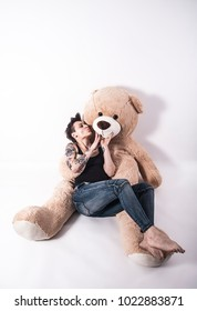 Tattooed natual looking woman playing with giant teddy bear