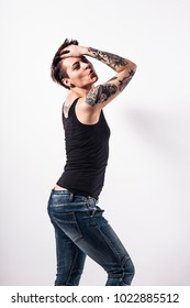 Tattooed natual looking woman with short black hair and face expression on bright background