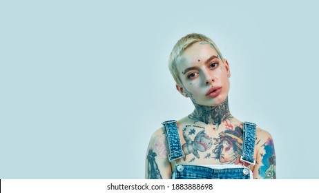 A tattooed and pierced white girl wearing denim overall standing and looking into a camera on a light blue color background