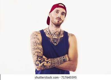 tattooed rap singer posing in studio on a white background