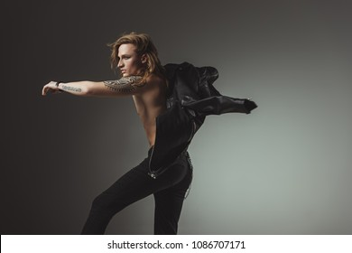tattooed rocker man with long hair in black leather jacket, isolated on grey