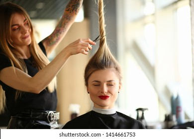 Tattooed Stylist Cutting Hair of Closed Eyes Woman. Hairdresser Using Scissors for Making Hairstyle for Female Client. Blonde Girl Getting Haircut in Beauty Salon. Hairstylist Styling New Hairdo