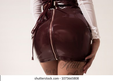 Tattooed woman beautiful bum, wearing latex dress