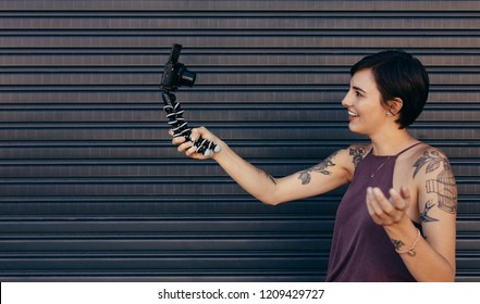 Tattooed woman vlogger recording her vlog content on a digital camera mounted on flexible tripod. Female making a video blog outdoors.