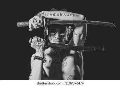 tattooed yakuza man. Man posing with sword with tattooed hands, neck and chest on black background. Defense, honor, torture, punishment, harakiri, tattoo concept.