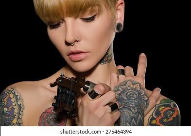tattooed young woman with tattoo machine, dark background