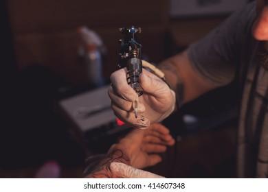 Tattooer is finishing his professional tattoo for customer