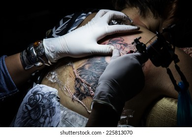tattooer showing process of making a tattoo. Tattoo design in pattern