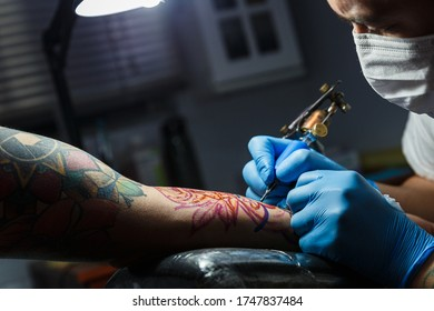 tattooist with his machine tattooing on the arm with the design drawn and using protective mask against covid 19, concept of art and design