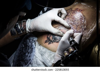 Tattooist making by professional artist is tattooing body sexy woman using machine in a creative design work studio. Process decoration ink artwork female skin.