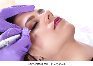 Tattooist making eyeliner with permanent make up on beautiful young girl in professional salon. Cosmetologist making tattoo make up with purple gloves and tools. Close up, selective focus