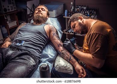 Tattooist posing in tatoo salon./Professional tattooist doing tattoo in tattoo studio.