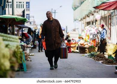 TAUNGGYI, MYANMAR - FEB 8: A Burmese nun going shopping at Taunggyi market in Myanmar on Feb 8, 2017.