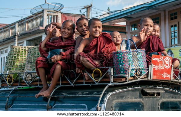 TAUNGGYI, MYANMAR - NOV 11, 2012:  young Buddhist monks travel on the roof of a van in Taunggyi near Inle Lake, November 11, 2012. They seem very amused.