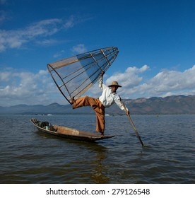 TAUNGGYI, SHAN, MAYANMAR - December, 06, 2014:  A local fisherman balances on his canoe, holding his net high and his oar in the water.