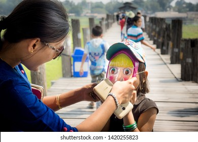 """Taungthaman/Myanmar-05.03.2017:Mother putting on her daughter a mask from the russian cartoon """"Masha and the bear"""""""