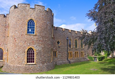 Taunton castle facade and tower, Somerset Museum, England, Uk, sunny bright summer morning with blue sky and some clouds, surrounded by a green park and meadow