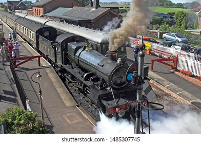 Taunton England May 2016. Taunton to Minehead steam train stationary in station making dark smoke from stack and steam from side. Carriages attached. Some passengers on platform. Sunny
