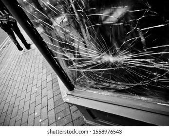 TAUNTON, SOMERSET, UK - November 13 2019: A vandalised shopfront, smashed window. A pedestrian walks past.
