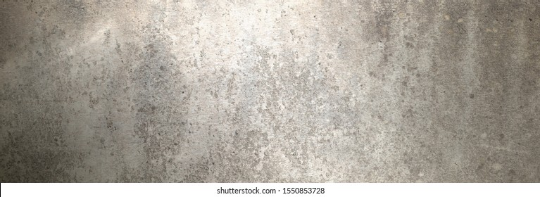 A taupe concrete wall as background for an advertising space on which light falls