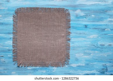 Taupe napkin on blue wooden table top view with copy space
