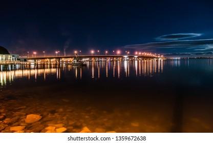 Tauranga Harbour Bridge illuminated street lights above and city lights below at night