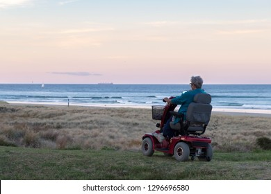 TAURANGA, NEW ZEALAND - 26 JANUARY 2019: An old woman rides on a electric powered wheelchair parked on the beach at sunset time, in a lonely atmosphere. Lonely widow old woman sits alone.