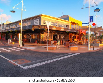 TAURANGA NEW ZEALAND - AUGUST 5 ; Tauranga street intersection with Crown & Badger pub on corner at dawn as sun rises and casts golden glow over buildings August 5 2008 Tauranga New Zealand