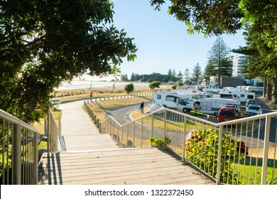 TAURANGA NEW ZEALAND - FEBRUARY 11 ; Wooden pathway along waterfront at bottom of Mount Maunganui past camping ground with sun burst through pohutukawa trees February 11 2019 Tauranga New Zealand