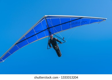 TAURANGA NEW ZEALAND - FEBRUARY 9; Hang glider pilot flying towards under bright blue wing and sky February 9 2019 Tauranga New Zealand