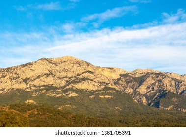 Taurus mountains at the first hour after sunrise. Mild sunlight, serene blue sky with white clouds. Treed slopes. Power transmission line on a slope.