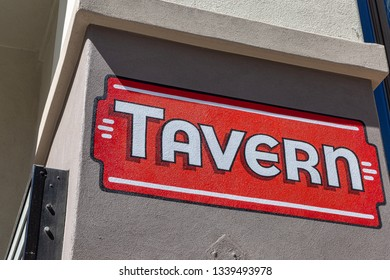 Tavern sign painted in red and white with black outline on builing wall