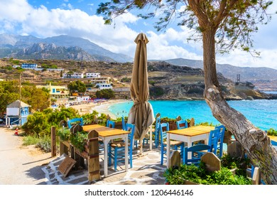 Taverna tables on terrace and view of beautiful beach in Lefkos village on coast of Karpathos island, Greece