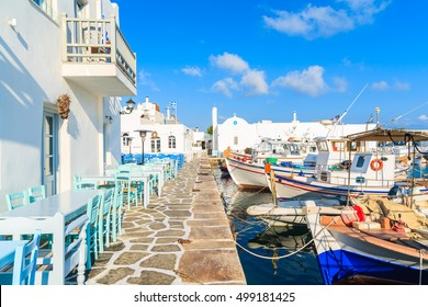 Taverna tables an traditional fishing boats in Naoussa port, Paros island, Greece
