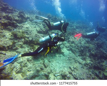 Taveuni, Fiji - August 18, 2017 - Woman SCUBA Diver Looking At Camer Underwater with three other divers.