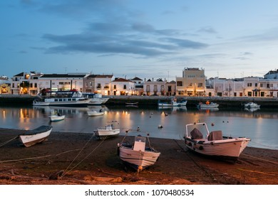 Tavira, Portugal - April 11; 2018: Fishing boats at the bank on the Gilao River in the Old Town of Tavira, Algarve, Portugal.