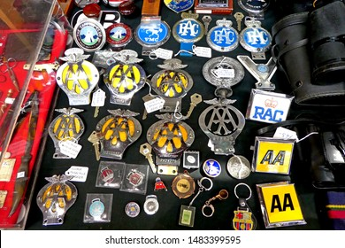 Tavistock England August 2019. Several car badges and key fobs. AA, RAC . Both vintage and modern designs. yellow and blue colours. In rows on market stall.
