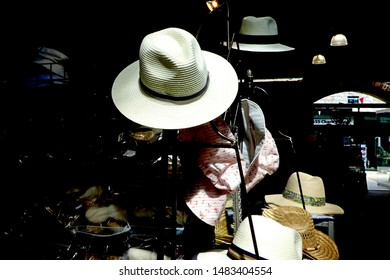 Tavistock England August 2019. White straw trilby hat on a stand lit by natural light against a dark background on a tall metal pole stand. Other hats in background. At jaunty angle.