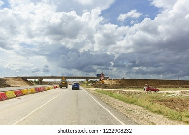 Tavrida highway, Crimea, Russia-September 7, 2018: Cloudy sky over the two-level junction of the new Tavrida highway under construction. The new section of the road is fenced with mobile road barriers