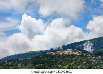 Tawang, Arunachal Pradesh, India. The ancient Buddist monastery set against the Himalayas with heavy clouds and surronded by the town at Tawang, Arunachal Pradesh, India.