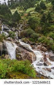 Tawang, Arunachal Pradesh, A natural waterfall gushing down the slopes of the Himalayas lined with large granit boulders near Tawang, Arunachal Pradesh, India.