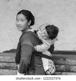 TAWANG, INDIA - SEPTEMBER 22, 2011: Yound mother carrying her baby on back during pilgrimage to the Buddhist Monastery on September 22, 2011 at Tawang, Arunachal Pradesh, India.