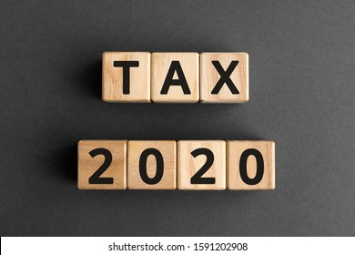 Tax 2020 - phrase from wooden blocks with letters, Tax time 2020 concept, top view gray background