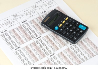 tax calculation form with calculator and pencil on the form