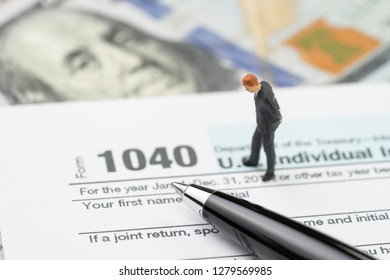 Tax calculation or submission concept, miniature people businessman or salaryman standing and thinking about revenue with pen on 1040 US individual income tax filling form with US dollar bill.