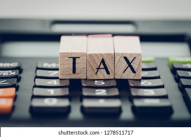 Tax calculation or submission concept, small wooden stamp with alphabet combine the word TAX on black calculator, individual income tax pay yearly.
