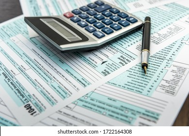 Tax concept 1040 tax form with calculator on desk. Finance time