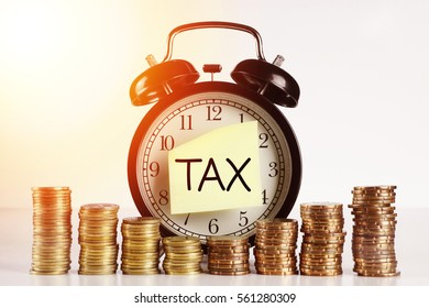 Tax Concept - A Clock with sticker note written TAX with gold coin on white background with flare effect