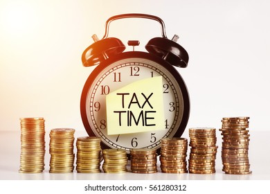 Tax Concept - A Clock with sticker note written TAX TIME with gold coin on white background with flare effect