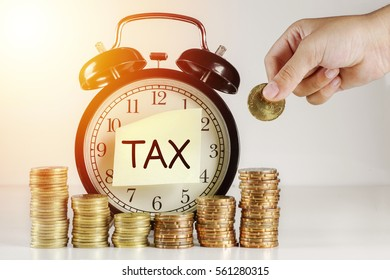 Tax Concept - A Clock with sticker note written TAX with a hand, gold coin on white background with flare effect